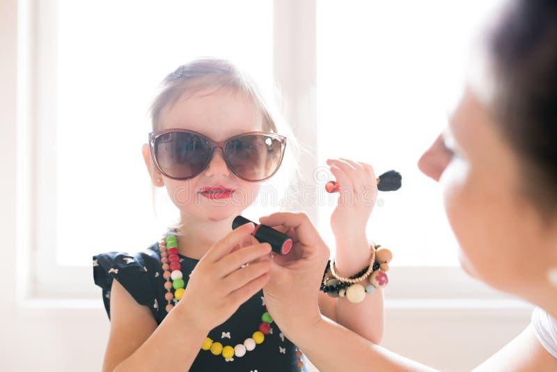 Bemuttern Sie Malereilippen ihrer netten kleinen Tochter mit Lippenstift lizenzfreie stockbilder