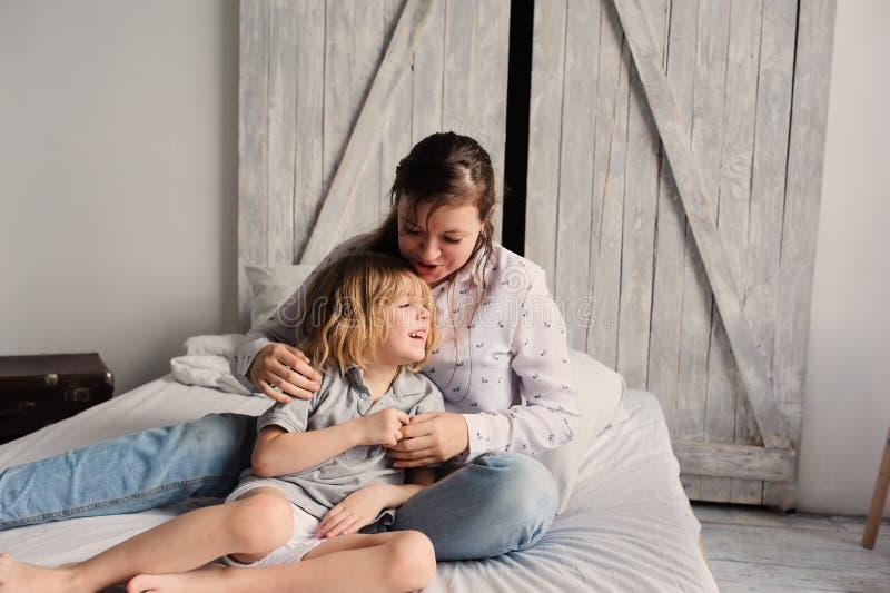 Bemuttern Sie mit Kindersohn auf Bett morgens spielen lizenzfreies stockbild
