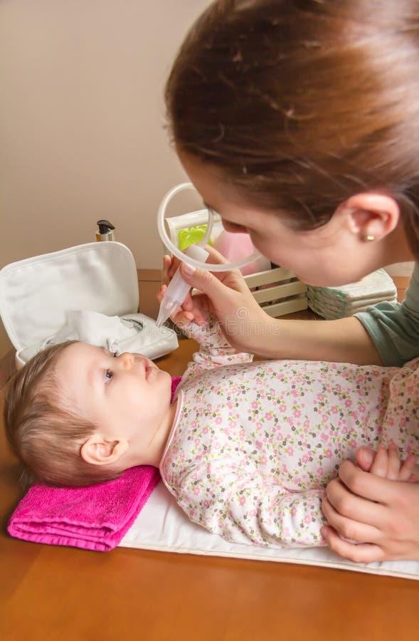Bemuttern Sie Reinigungsschleim des Babys mit nasalem Saugapparat stockfotografie