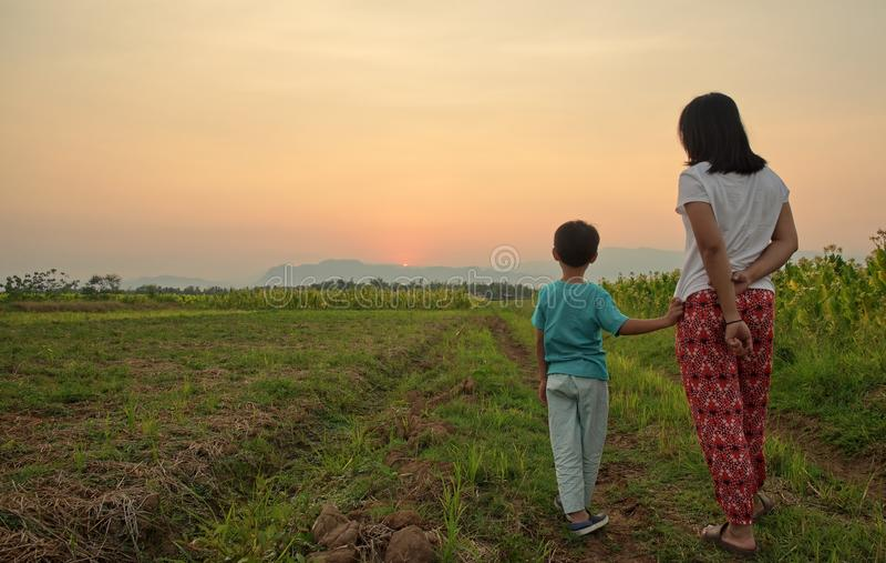 Bemuttern Sie Stellung mit ihrem Sohn auf dem Feld und aufpassenden Bergen bei Sonnenuntergang stockbild