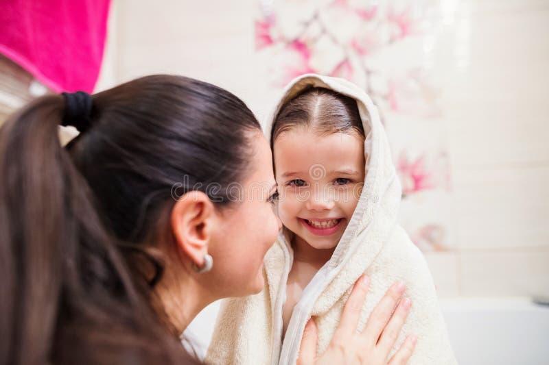 Bemuttern Sie trocknende Tochter, nachdem Sie das Bad genommen haben, eingewickelt im Tuch stockbild
