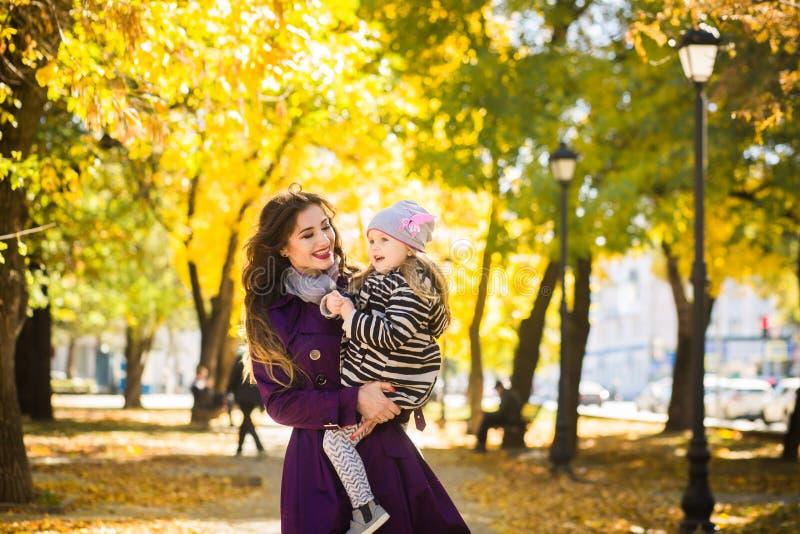 Bemuttern Sie und ihr Kindermädchen, das zusammen draußen auf Herbstweg in der Natur spielt lizenzfreie stockfotografie