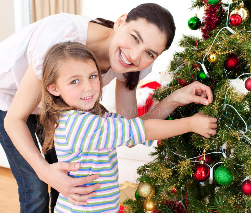 Bemuttern Sie und ihr Mädchen, das einen Weihnachtsbaum verziert stockfotografie