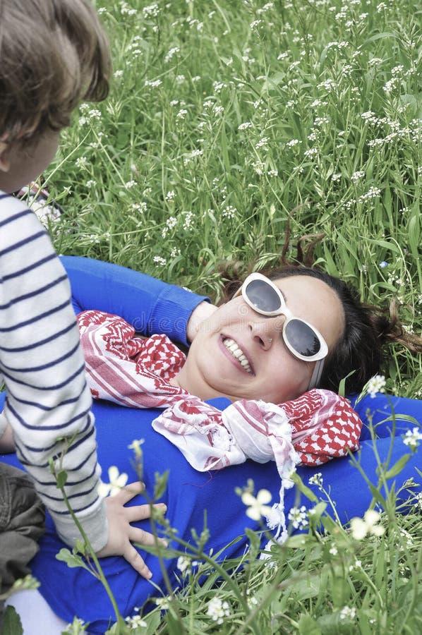 Bemuttern Sie und ihr Sohn, der im Frühjahr auf Gras liegt lizenzfreie stockfotografie