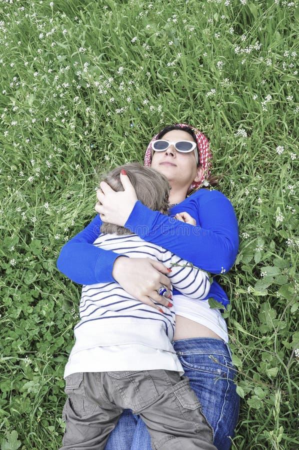 Bemuttern Sie und ihr Sohn, der im Frühjahr auf Gras liegt lizenzfreie stockbilder