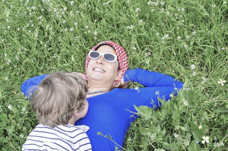 Bemuttern Sie und ihr Sohn, der im Frühjahr auf Gras liegt stockbilder