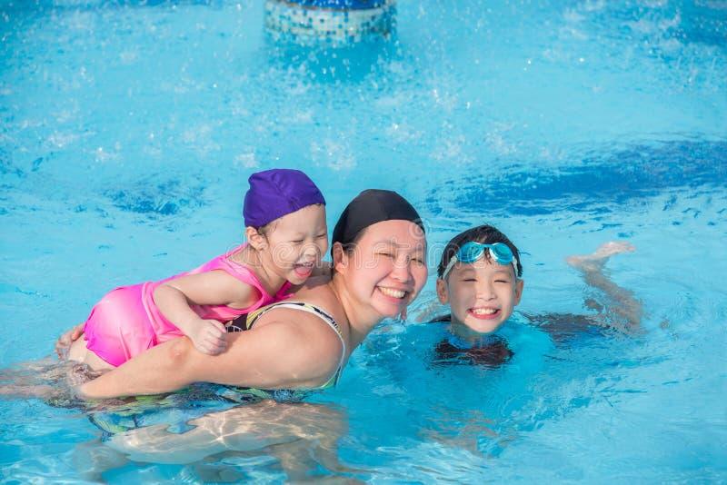 Bemuttern Sie und ihre Kinder, die im Swimmingpool glücklich sind lizenzfreie stockbilder
