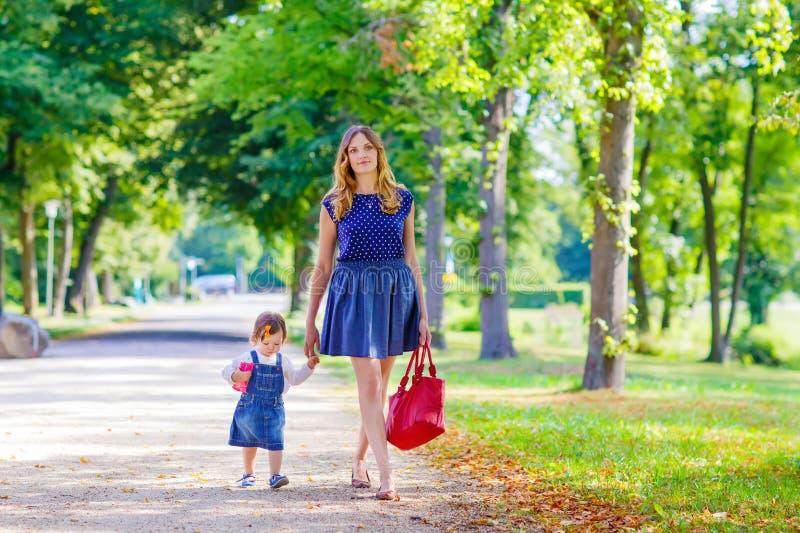 Bemuttern Sie und ihre kleine Tochter, die in Sommer geht lizenzfreies stockfoto