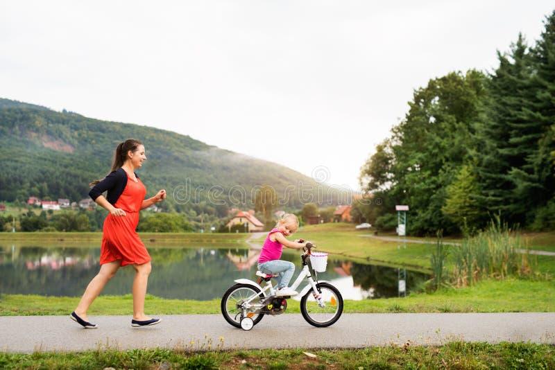 Bemuttern Sie und ihre nette kleine Tochter in der Natur lizenzfreie stockfotos
