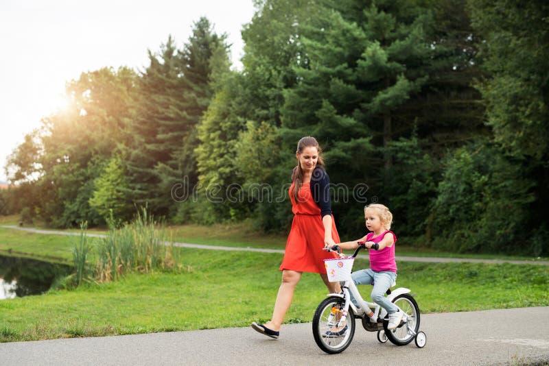Bemuttern Sie und ihre nette kleine Tochter in der Natur stockfoto