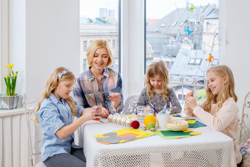 Bemuttern Sie und ihre Töchter, die Ostereier malen und verzieren lizenzfreie stockbilder