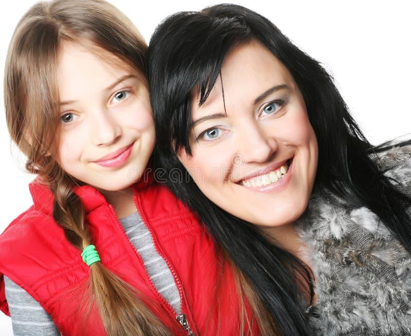 Bemuttern Sie und ihre Tochter, die an der Kamera lächelt stockfoto