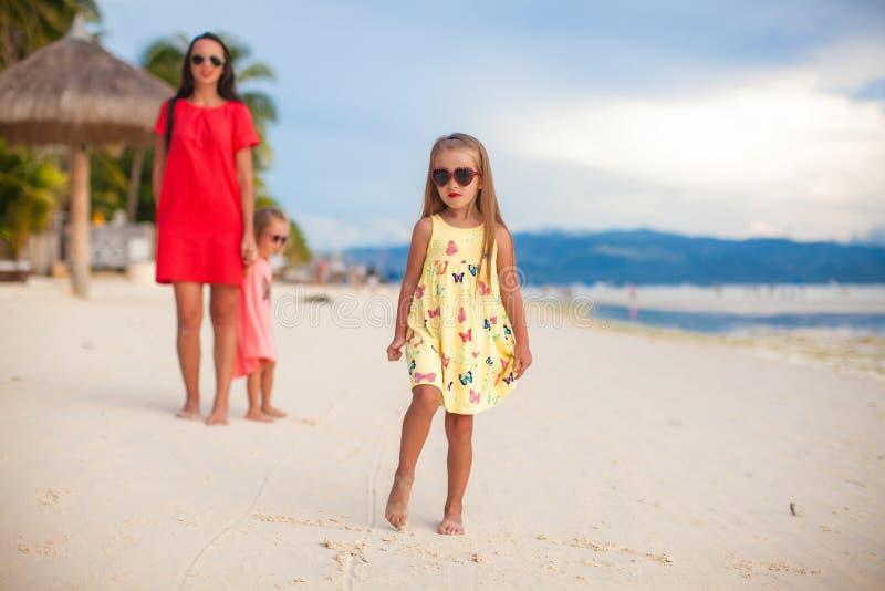 Bemuttern Sie und zwei ihre Kinder am exotischen Strand auf Sonnenuntergang stockbild