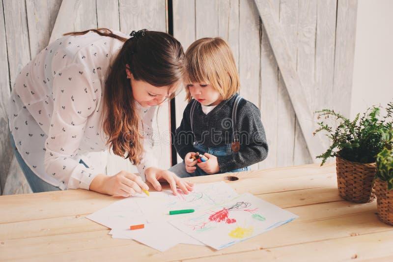 Bemuttern Sie unterrichtenden Kleinkindjungen, um mit Bleistiften zu Hause zu zeichnen lizenzfreies stockfoto