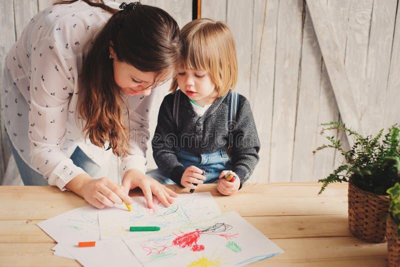 Bemuttern Sie unterrichtenden Kleinkindjungen, um mit Bleistiften zu Hause zu zeichnen stockfoto