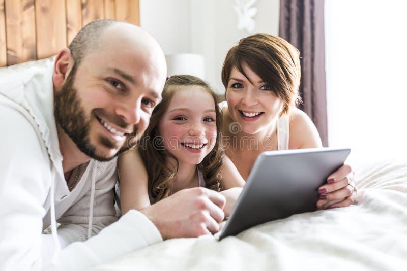 Bemuttern Sie Vater und ihr Kind mit der digitalen Tablette, die sich zu Hause entspannt lizenzfreies stockbild