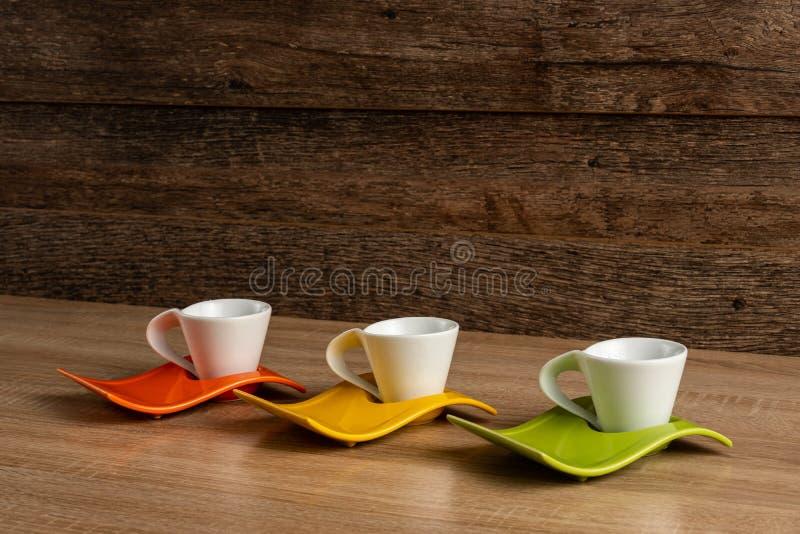 Benägen sikt från vänster till höger för sida av stället för koppar för vitt kaffe på tre färgplattor royaltyfria foton