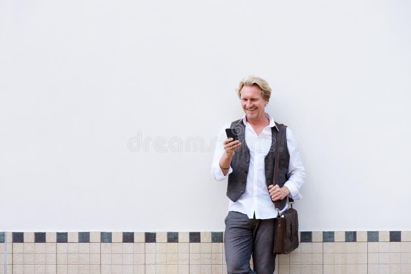 Benägenhet för äldre man mot väggen med mobiltelefonen och påsen royaltyfri foto