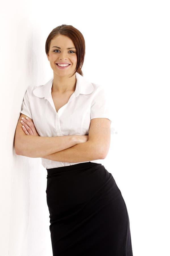 Benägenhet för affärskvinna mot en vägg royaltyfri bild