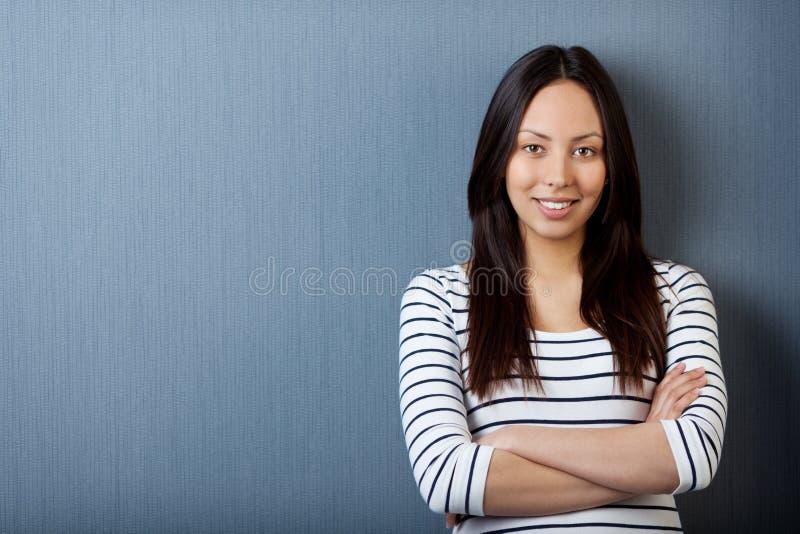 Benägenhet för tonårs- flicka mot den gråa väggen arkivbild