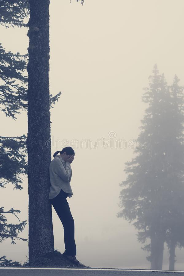 Benägenhet för ung kvinna mot träd med framsidan som döljas i händer och gråt arkivfoto