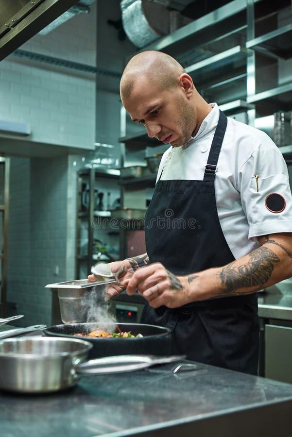 Benötigen Sie mehr Gewürze Vertikales Foto des Restaurantchefs mit einigen Tätowierungen, die ein spezielles Gewürz frischen geko lizenzfreie stockfotos