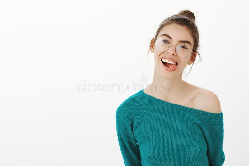 Ben altijd zelf Portret die van onbezorgde gelukkige Kaukasische vrouw in glazen, vreugdevol terwijl het tonen van tong glimlache royalty-vrije stock foto's