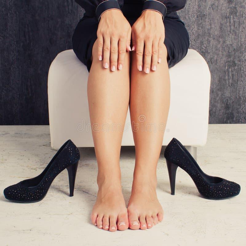 Ben av affärskvinnan som sitter i dräkt med skor arkivfoto