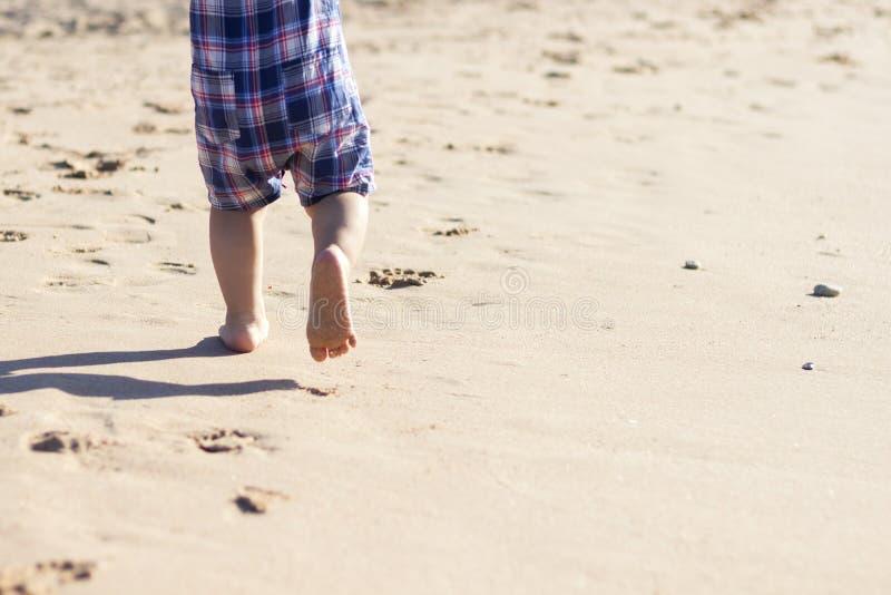 Ben av barnställningen på stranden Behandla som ett barn fot i sanden volleyboll för sommar för bakgrundsbollstrand härlig tom So arkivfoto