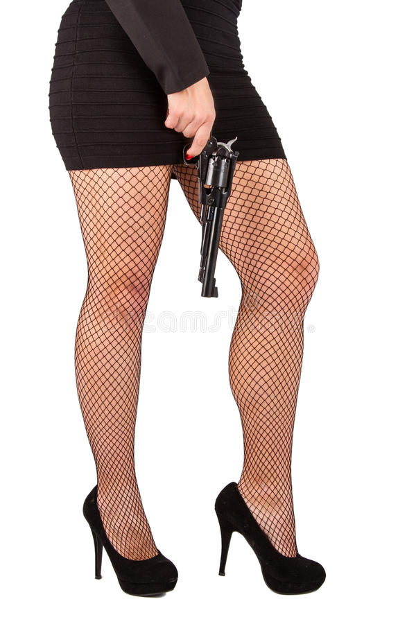 Ben av den farliga kvinnan med handeldvapen- och svartskor arkivfoto