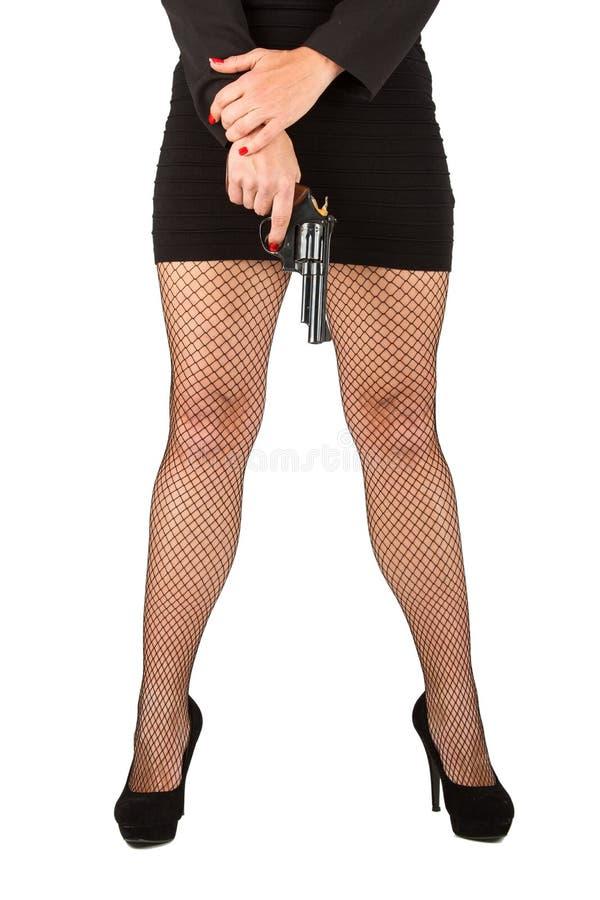 Ben av den farliga kvinnan med handeldvapen- och svartskor royaltyfri foto