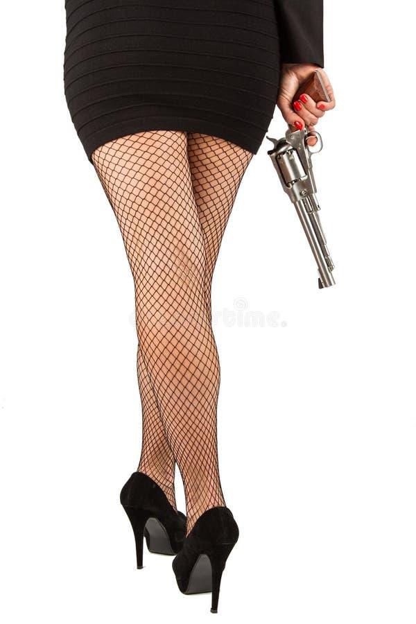 Ben av den farliga kvinnan med handeldvapen- och svartskor fotografering för bildbyråer