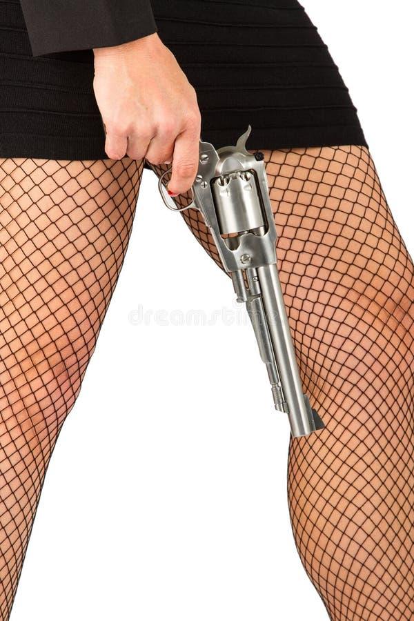 Ben av den farliga kvinnan med handeldvapen- och svartskor royaltyfria foton