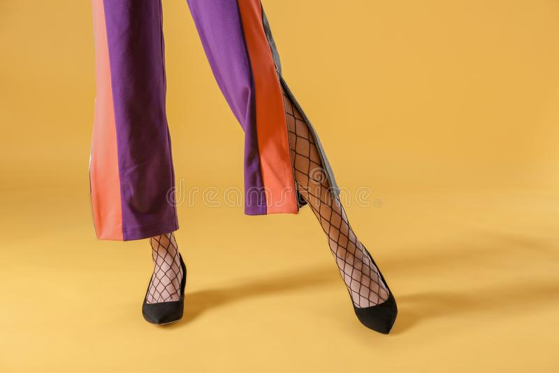 Ben av den härliga unga kvinnan i strumpbyxor och byxa på färgbakgrund arkivfoton