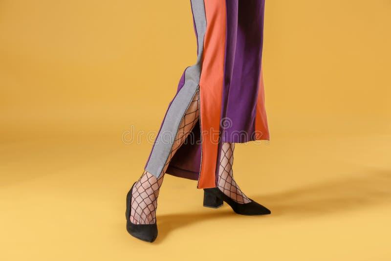 Ben av den härliga unga kvinnan i strumpbyxor och byxa på färgbakgrund royaltyfri bild