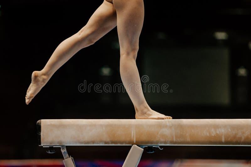 Ben av den kvinnliga gymnasten på balansbommen arkivbilder