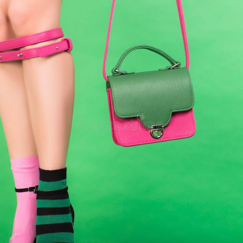 Ben av den modekvinna- och för kvinna` s handväskan på en grön bakgrund arkivfoto