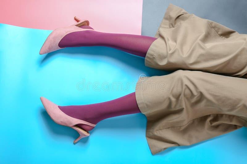Ben av den unga kvinnan i strumpbyxor och byxa på färgbakgrund fotografering för bildbyråer