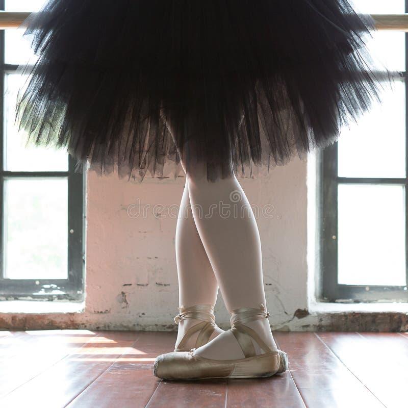 Ben av en ballerinacloseup Benen av en ballerina i gammal pointe Repetitionballerina i korridoren Konturljus från fönstret arkivbild