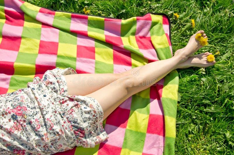 Ben av en härlig ung kvinna i sommarklänning på den färgrika picknickfilten royaltyfria foton