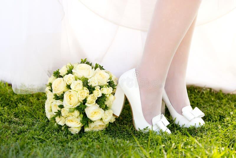 Ben av flickan eller bruden i vitskor med pilbågar och den runda bröllopbuketten royaltyfri bild
