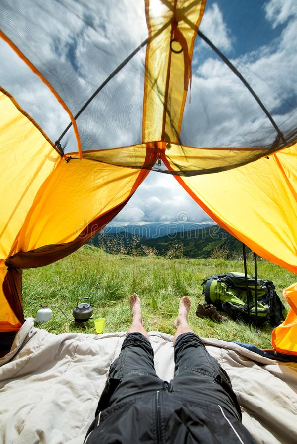 Ben av handelsresanden i ett tält med turist- utrustning utomhus royaltyfri fotografi