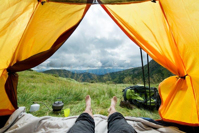 Ben av handelsresanden i ett tält med turist- utrustning utomhus arkivbilder