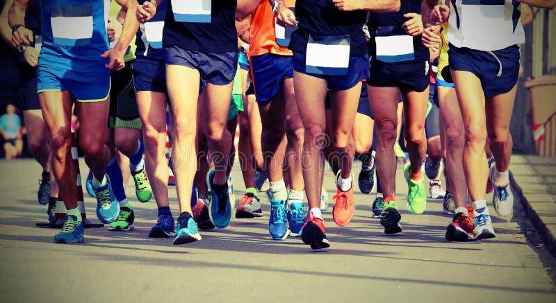 Ben av idrottsman nen som kör maraton på staden med gammal vint royaltyfria foton