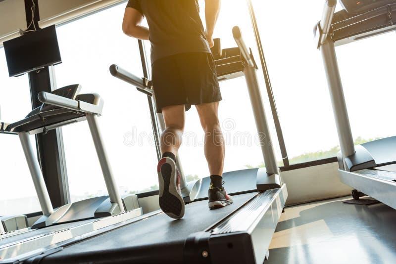 Ben av idrottsmannen som kör på trampkvarnen i konditionidrottshallmitt Sport och sunt livsstilbegrepp Folkgenomkörare och övning royaltyfria bilder