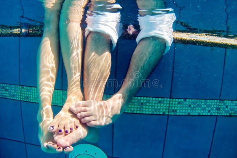 Ben av mannen och kvinnan i den undervattens- pölen royaltyfria bilder