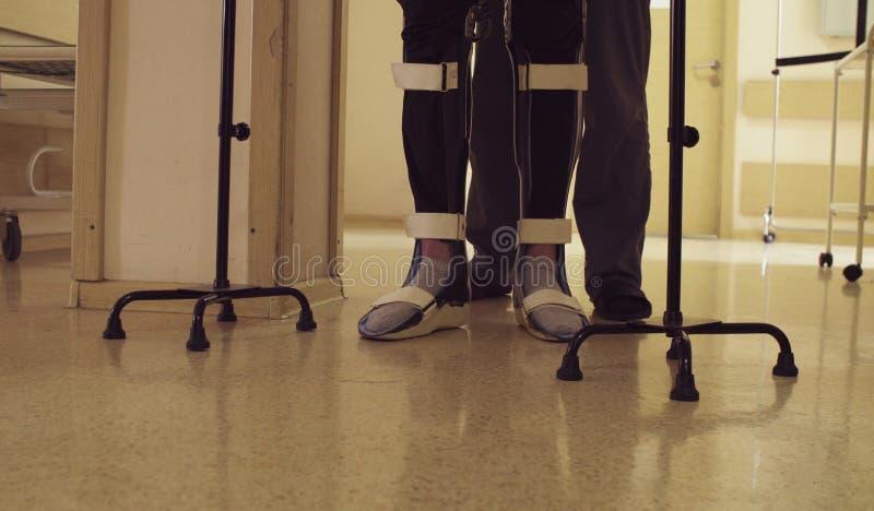 Ben av ogiltigt i orthosisen som går med service av gå rotting två royaltyfri foto