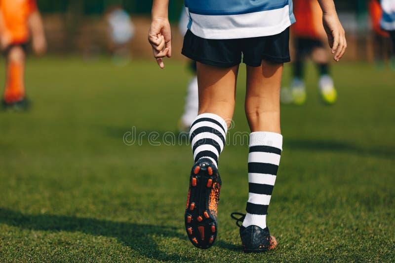 Ben av pojkefotbollsspelaren i kängafotbolldubbar Spelare som går på fotbollfält för grönt gräs på stadion arkivfoto