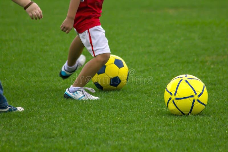 Ben av ungar sparkar fotboll royaltyfria foton