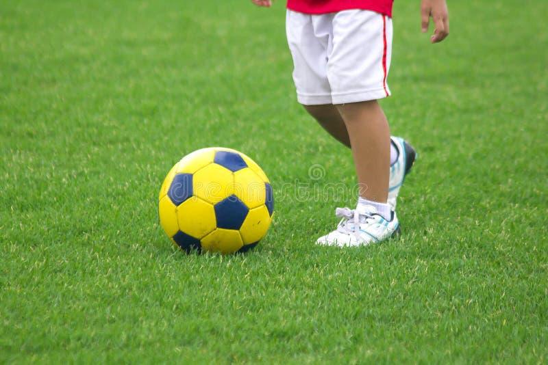 Ben av ungar sparkar fotboll royaltyfri foto